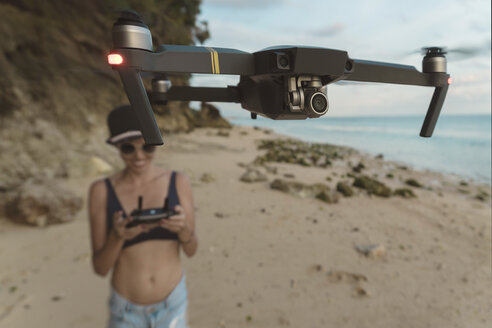Indonesia, Bali, Nusa Dua, woman flying drone at the beach - KNTF02711