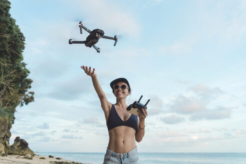 Indonesia, Bali, Nusa Dua, woman flying drone at the beach - KNTF02714