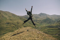 Rear view of happy woman with arms raised jumping on mountain against clear sky during sunny day - CAVF61610