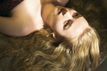 High angle view of thoughtful woman with blond hair lying on bed at home - CAVF61622