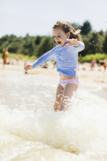 Playful girl jumping in sea on shore during sunny day - CAVF61634