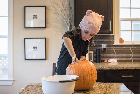 Girl making jack o' lantern at home during Halloween - CAVF61637
