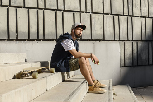 Side view of confident man listening music while sitting with skateboard on steps against wall - CAVF61652