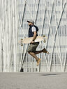Side view of man holding skateboard while jumping on road against building in city during sunny day - CAVF61670