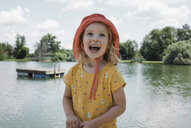 Happy girl wearing hat looking up while standing by lake against cloudy sky at park - CAVF61718