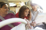 Family with map riding in car on road trip - CAIF22791