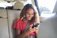 Tween girl using smart phone in back seat of car - CAIF22803