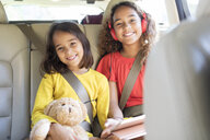 Portrait happy sisters with teddy bear riding in back seat of car - CAIF22809