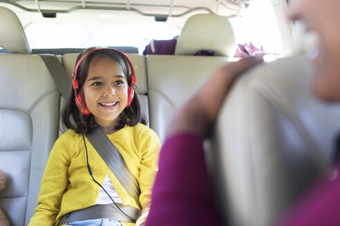 Smiling girl with headphones riding in back seat of car - CAIF22821