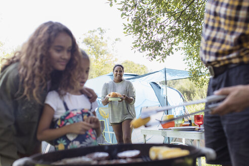 Family barbecuing at campsite - CAIF22833