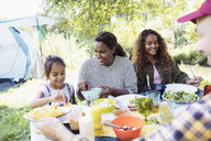 Happy family enjoying lunch at campsite table - CAIF22851