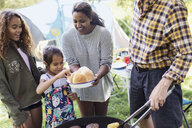 Family barbecuing hamburgers at campsite - CAIF22869