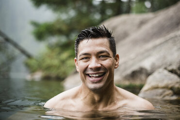 Portrait smiling, handsome young man swimming in lake - CAIF22875