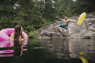Playful young man with inflatable ring jumping into remote lake, Squamish, British Columbia, Canada - CAIF22887