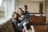 Portrait happy mother and children cuddling on living room sofa - CAIF22893