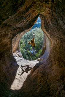 Young woman jumping in cave entrance, Cova Simanya,Barcelona, Spain - AFVF02479