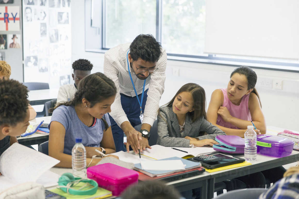 Male teacher helping junior high school girl students at desk in classroom - CAIF22911 - Robert Daly/Westend61