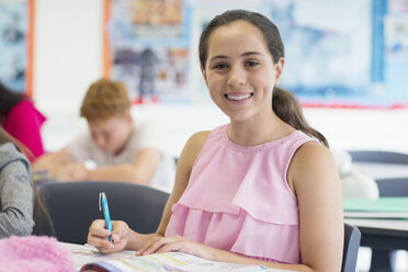Portrait smiling, confident junior high school girl student doing homework in classroom - CAIF22920
