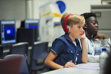Focused junior high school boy with headphones in classroom - CAIF22941