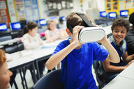 Junior high school boy student using virtual reality simulator glasses in classroom - CAIF22944