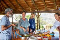 Happy friends enjoying healthy meal in hut during yoga retreat - CAIF22965
