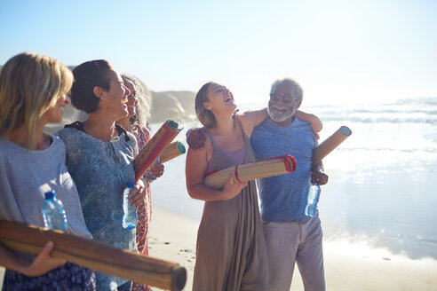 Happy friends with yoga mats bonding on sunny beach during yoga retreat - CAIF23007