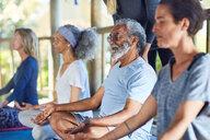 Serene senior man meditating during yoga retreat - CAIF23028