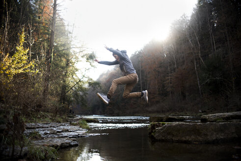 Side view of teenage boy jumping over river against trees in forest - CAVF61743