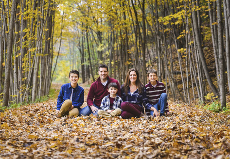 Portrait of smiling family sitting on dry leaves amidst trees in forest - CAVF61746