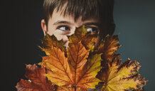 Close-up of boy looking away while covering face with autumn leaves against colored background - CAVF61752