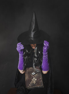 Woman dressed in witch costume sitting against black background during Halloween - CAVF61755