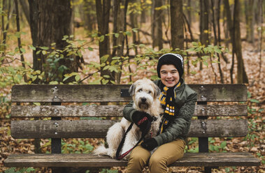Portrait of smiling boy sitting with dog on bench in forest during autumn - CAVF61764