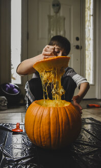 Boy removing seeds from fresh pumpkin at home - CAVF61767