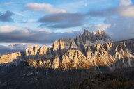 Scenic view of Dolomites against cloudy sky during sunset in forest - CAVF61797