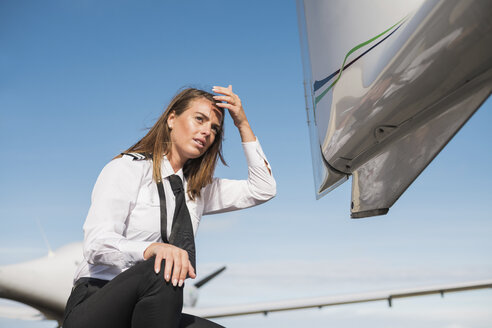 Low angle view of female engineer looking away while crouching by airplane against blue sky during sunny day - CAVF61806