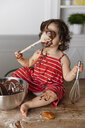Cute baby girl eating chocolate while sitting on wooden table against wall at home - CAVF61818