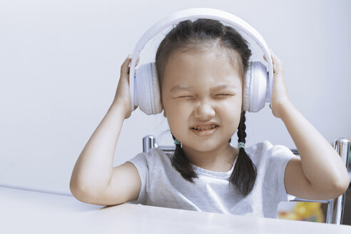 Portrait of little girl listening music with white cordless headphones - AZF00128