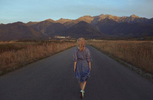USA, California, back view of strawberry blonde woman walking on country road - AZF00131