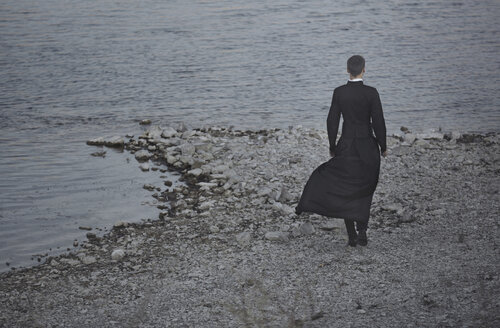 Germany, Bavaria, back view of young pastor standing at lake shore - AZF00134