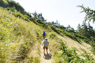 Rear view of brothers walking on trail against clear sky at Fort Ebey State Park - CAVF61836
