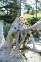 Portrait of cute smiling baby boy standing by driftwood at beach against trees during sunny day - CAVF61839