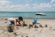 Shirtless boy making sandcastles at beach during sunny day - CAVF61851