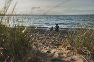 Rear view of father and son sitting at beach by sea during sunset - CAVF61854
