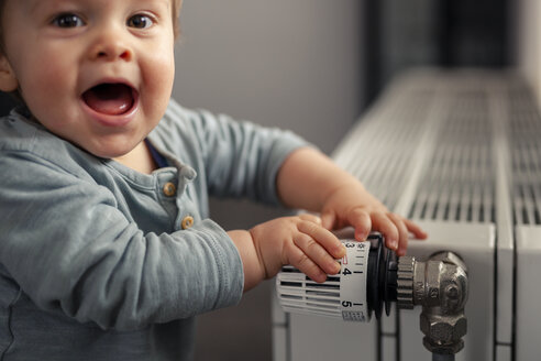 Excited baby boy playing with thermostat of heater - SEBF00019