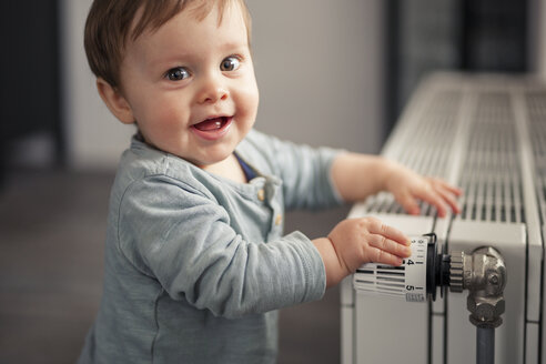 Portrait of smiling baby boy playing with thermostat of heater - SEBF00022