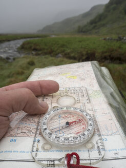 Great Britain, Scotland, Knoydart Peninsula, Hand holding compass and map during rain - HUSF00023