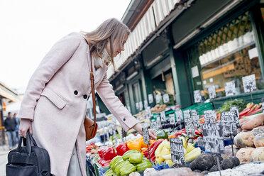 Austria, Vienna, young woman choosing vegetables at Naschmarkt - ZEDF01928