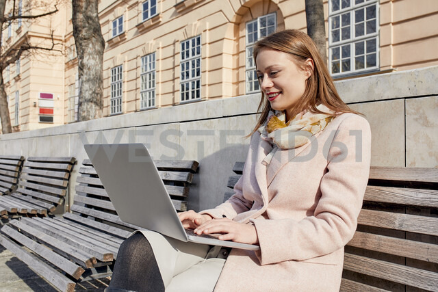 Austria, Vienna, smiling young woman sitting on bench at MuseumsQuartier using laptop - ZEDF01931