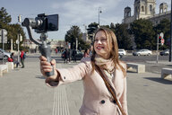 Austria, Vienna, portrait of smiling young woman using selfie-stick for taking photo - ZEDF01940