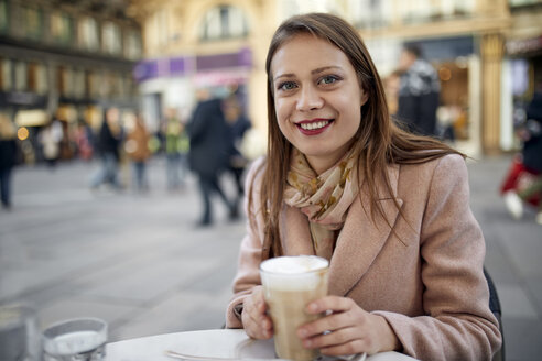 Austria, Vienna, portrait of smiling young woman drinking coffee at pavement cafe - ZEDF01943